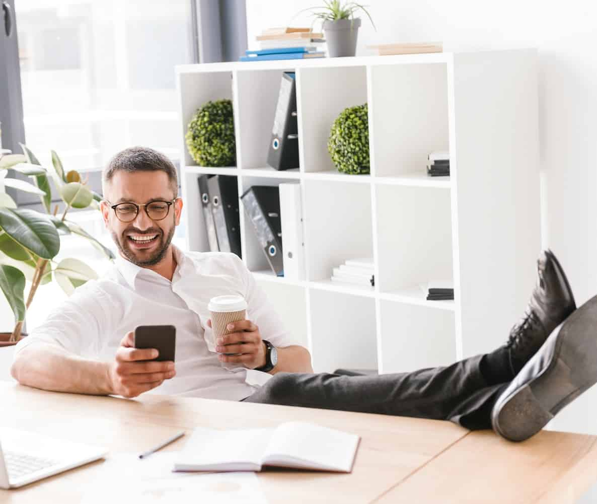 Image of cheerful handsome man in formal wear sitting in office with legs at table, and using black smartphone
