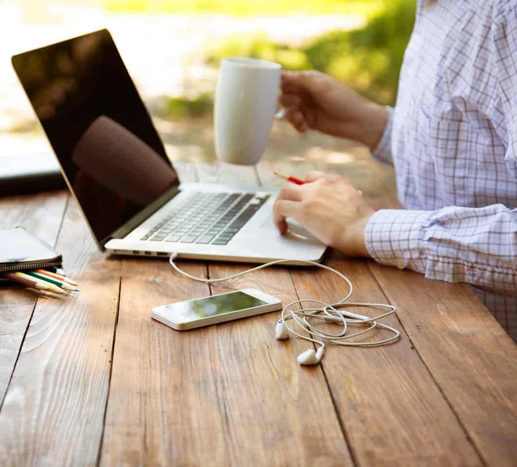 Casual dressed man sitting at wooden desk inside garden working on computer pointing with colour pen drinking coffee gadgets dropped around on table side view